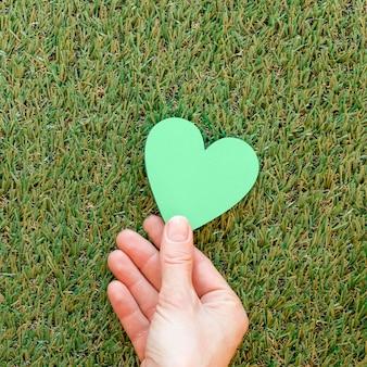 Person, die ein grünes herz auf gras hält