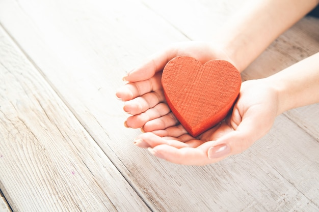 Person, die ein handgemachtes rotes herz in ihren händen hält