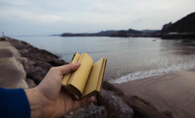 Person, die ein kleines notizbuch mit einem verschwommenen meer in candas, asturien, spanien hält