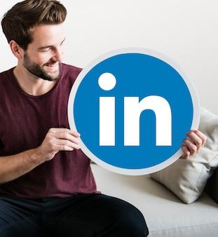 Person, die ein Linkedin-Symbol hält