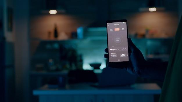 Person, die ein mobiltelefon mit high-tech-anwendung in einem intelligenten haus hält, steuert die lichter mit ...