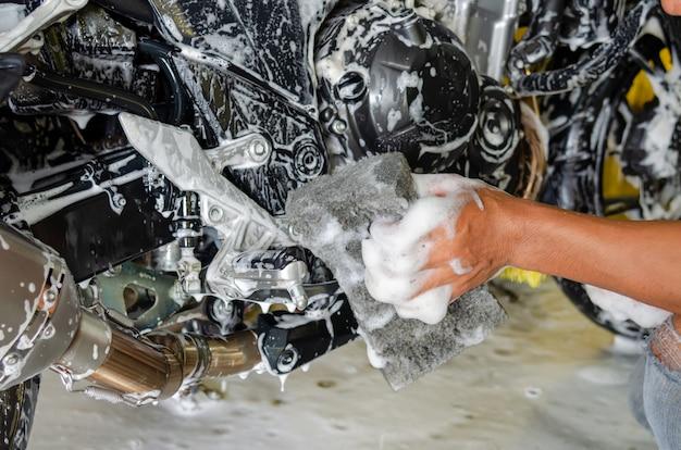 Person, die ein motorrad wäscht