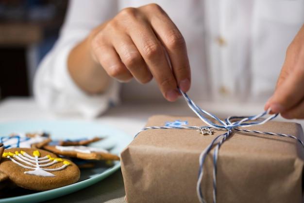 Person, die ein schönes verpacktes geschenk öffnet