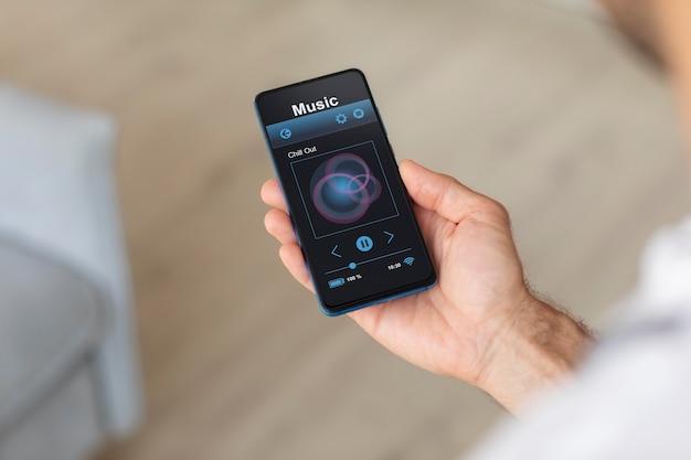 Person, die ein smartphone mit einer hausautomatisierungs-app hält