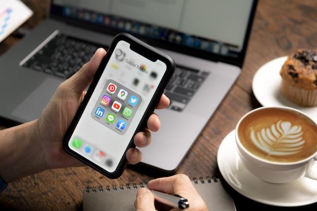 Person, die ein smartphone mit symbolen der sozialen medien auf dem bildschirm im café hält