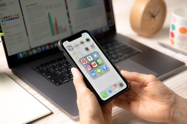 Person, die ein smartphone mit symbolen der sozialen medien auf dem bildschirm zu hause hält