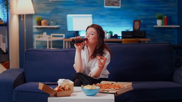 Person, die ein stück pizza auf der couch isst und in die kamera schaut