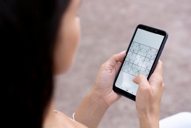 Person, die ein sudoku-spiel auf einem smartphone spielt