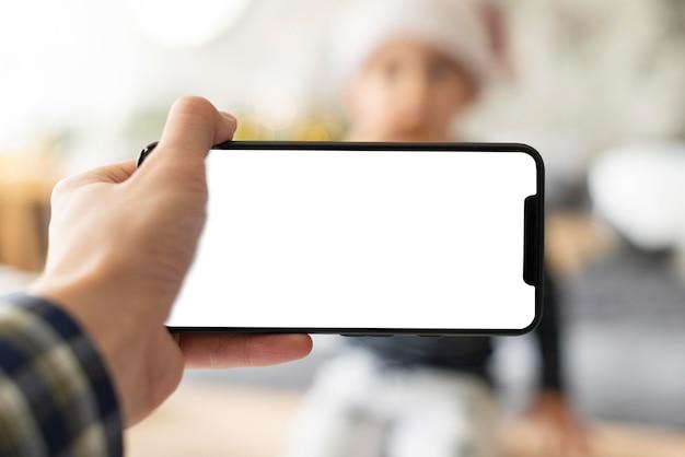 Person, die ein telefon mit leerem bildschirm hält