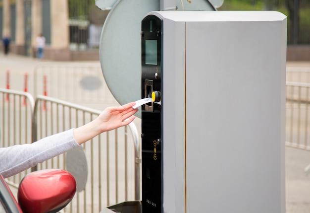 Person, die ein ticket in den parkautomaten einführt oder aus diesem entfernt.