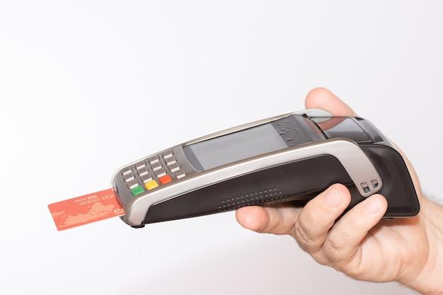 Person, die ein zahlungsterminal mit einer roten kreditkarte hält, wischte durch den automaten