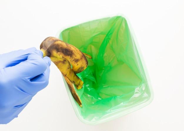 Person, die eine bananenschale in den behälter wirft