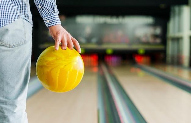 Person, die eine gelbe bowlingkugel hält