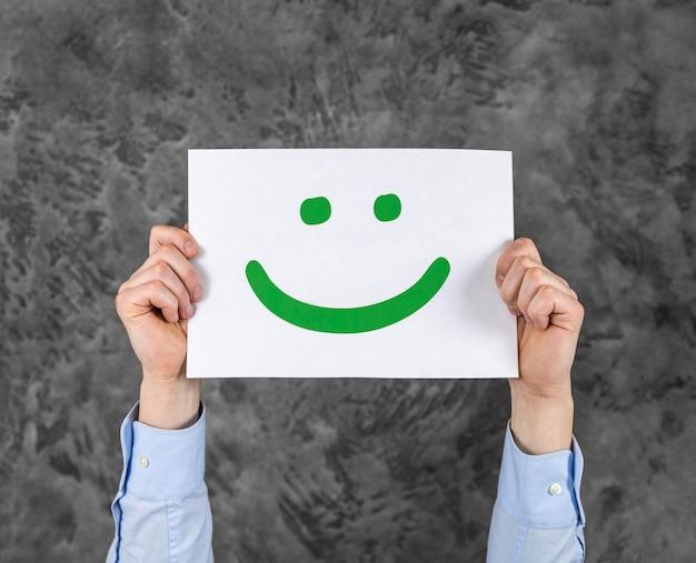 Person, die eine karte mit einem smiley hält