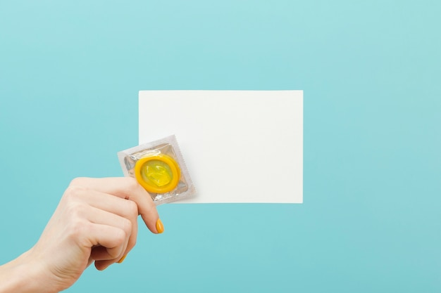 Person, die eine leere karte und ein kondom hält