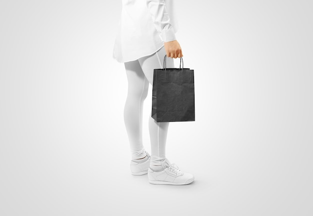 Person, die eine leere schwarze bastelpapiertüte hält