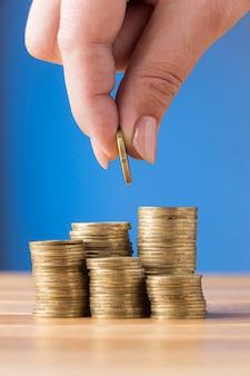 Person, die eine münze auf einen stapel münzen legt