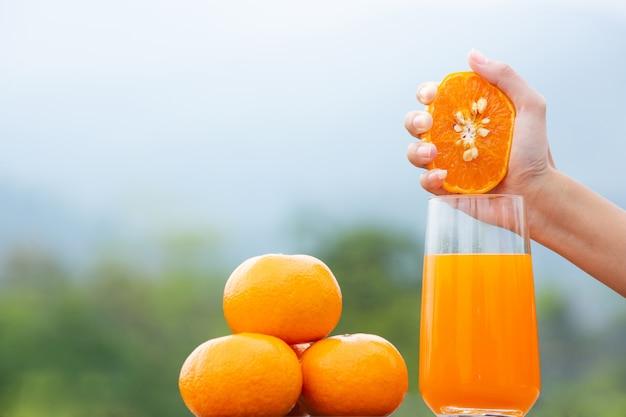 Person, die eine orange frucht in ihrer hand hält und sie in einem glas zusammendrückt