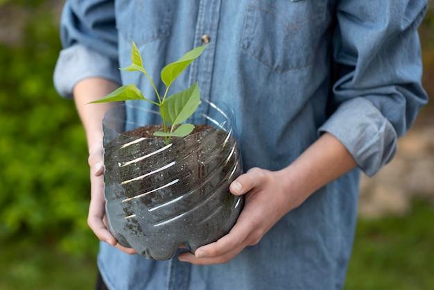 Person, die eine pflanze in einem plastiktopf hält