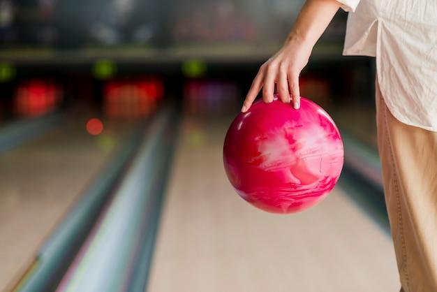 Person, die eine rote bowlingkugel hält