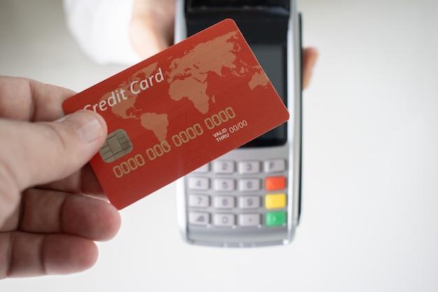 Person, die eine rote kreditkarte mit einem verschwommenen zahlungsterminal im hintergrund hält