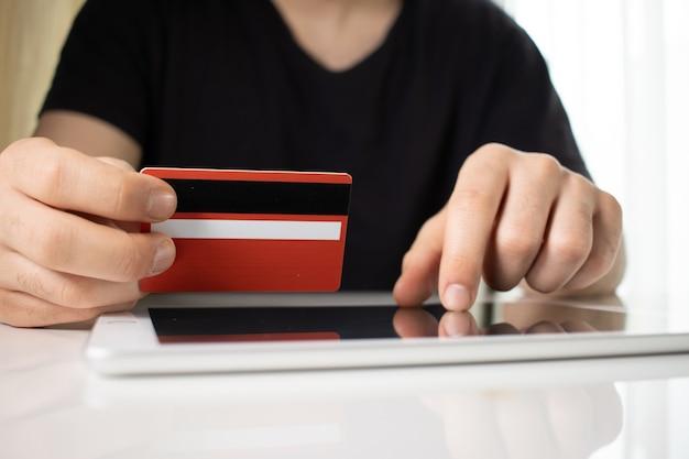 Person, die eine rote kreditkarte über einer tablette auf einer weißen oberfläche hält