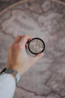 Person, die eine runde lupe auf einem unscharfen globus hält