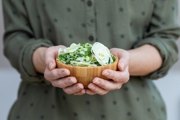 Person, die eine schüssel salat aus dehydrierten zwiebeln hält