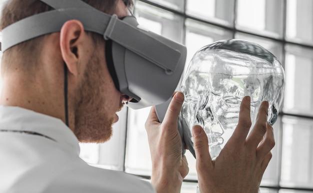 Person, die eine virtual-reality-brille trägt, die eine transparente schaufensterpuppe hält