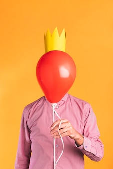 Person, die einen ballon auf orange hintergrund hält