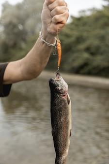Person, die einen fisch mit einer stange fischt