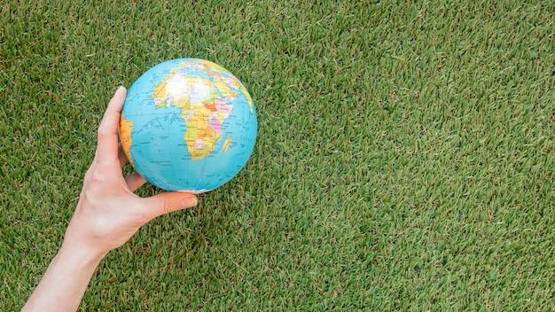 Person, die einen globus auf gras mit kopienraum hält