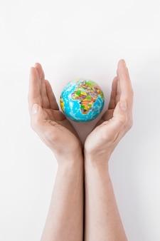 Person, die einen globus auf weißem hintergrund hält