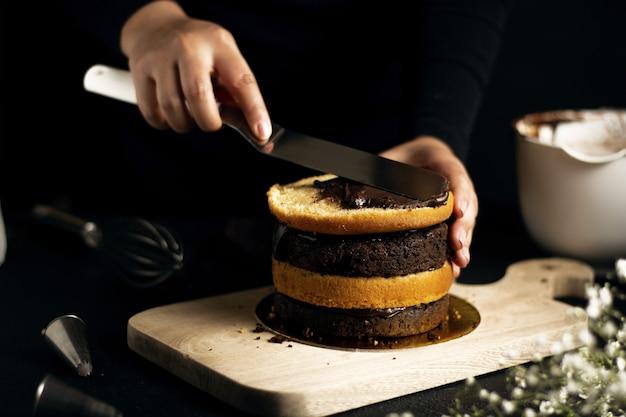 Person, die einen kleinen kuchen mit schokoladen- und vanilleschichten vorbereitet