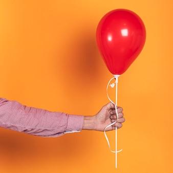 Person, die einen roten ballon auf orange hintergrund hält