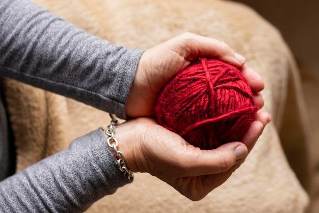 Person, die einen roten faden zum stricken hält