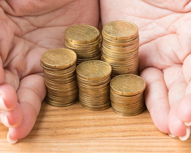 Person, die einen stapel münzen hält