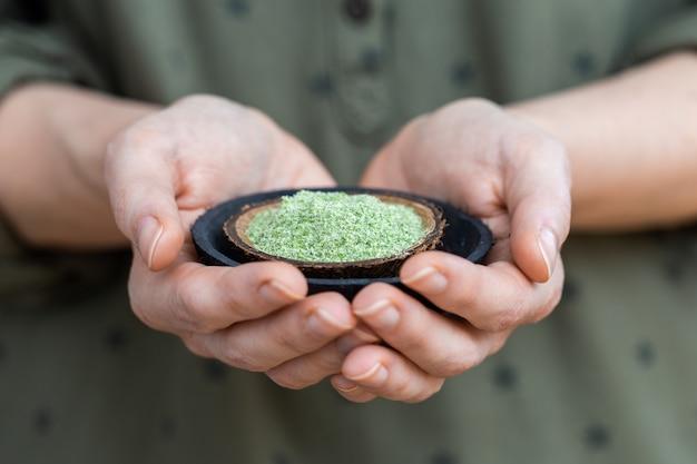Person, die einen teller des grünen pulvers hält, das für rohe vegane nahrungsmittel verwendet wird