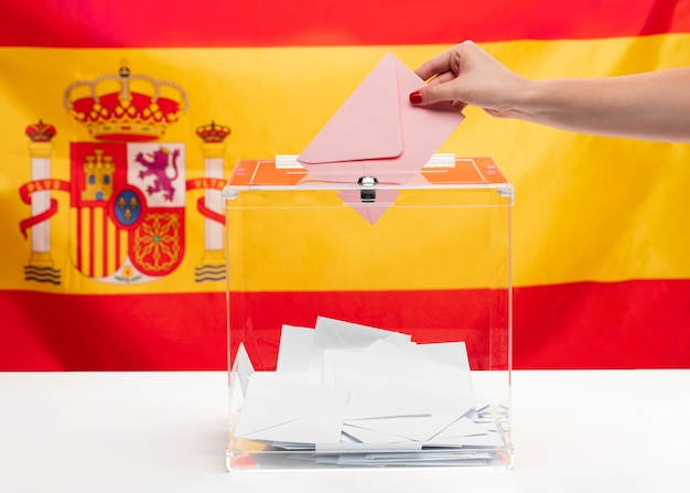 Person, die einen umschlag in einen abstimmungskasten und in einen spanischen flaggenhintergrund einsetzt
