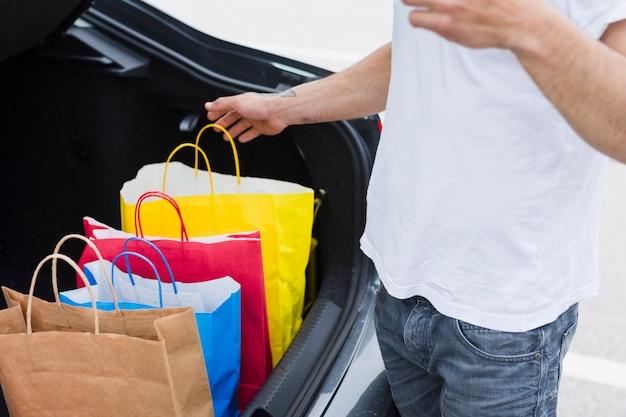 Person, die einkaufstaschen im auto hält
