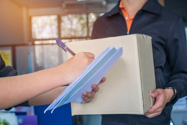 Person, die empfang des lieferungskastenpakets unterzeichnet