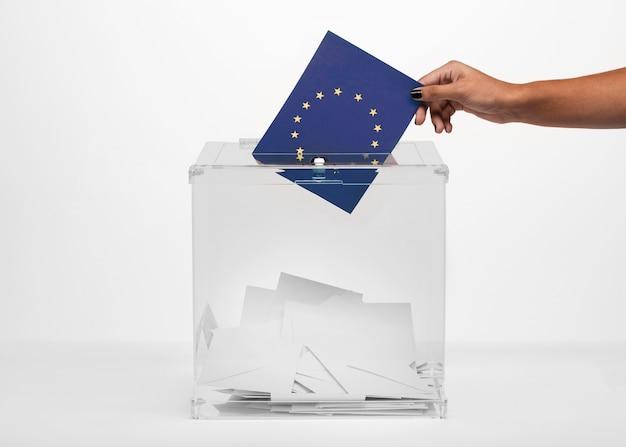 Person, die flaggenkarte der europäischen gemeinschaft in wahlurne setzt