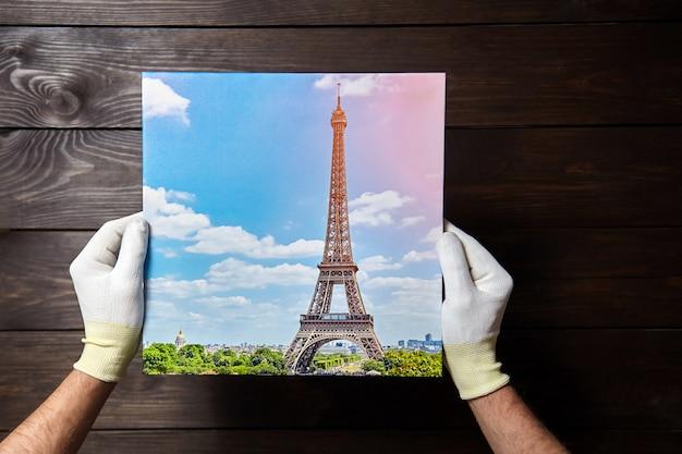 Person, die foto hält, das auf leinwand auf holztisch gedruckt wird
