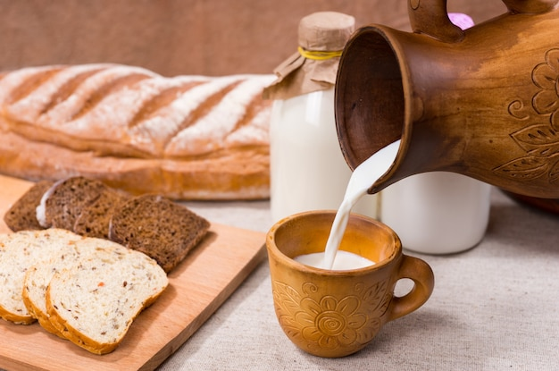 Person, die frische cremige bauernmilch in einen rustikalen keramikbecher mit geschnittenem frischem brot auf einem brett für ein gesundes frühstück gießt