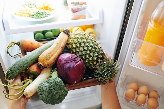 Person, die gemüse aus dem kühlschrank nimmt