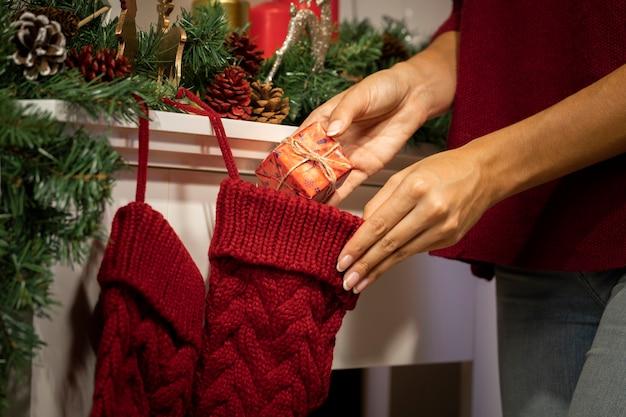 Person, die geschenk in weihnachtsstrumpf einsetzt