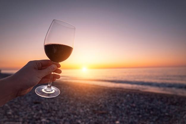 Person, die glas rotwein während des beobachten des sonnenuntergangs und des genießens des seeurlaubs hält