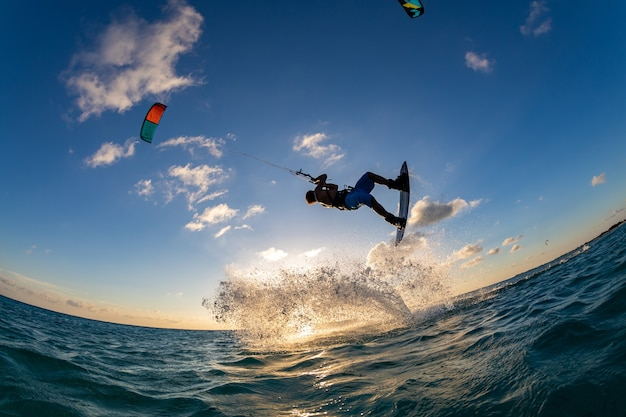 Person, die gleichzeitig beim kitesurfen surft und einen fallschirm fliegt. bonaire, karibik