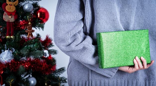 Person, die grünes funkelnpackpapier weihnachtsgeschenk hält