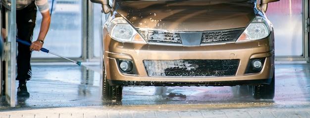 Person, die ihr auto an einer station mit einem speziellen reiniger wäscht, autowaschdienste